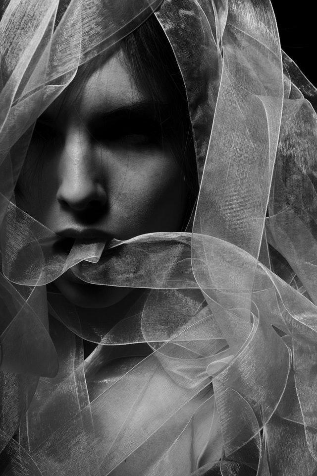 SW Portrait von einer Braut, deren Gesicht mit weißem Tüll Band umwickelt wurde.