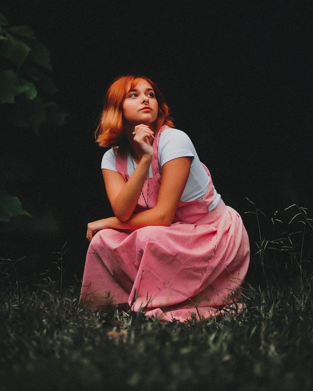 rothaariges Mädchen in rotweiß gestreiftem Kleid