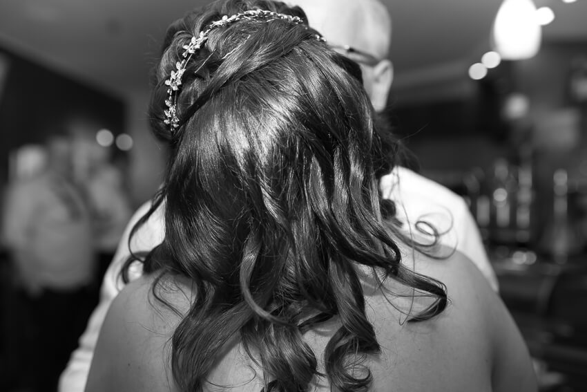 Brautpaar küsst sich, man sieht die schönen Haare der Braut von hinten.