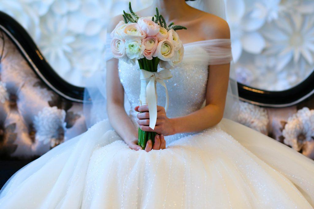 sitzende Frau in weißem Brautkleid in A-Linienform