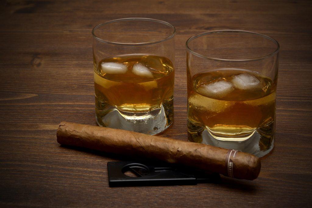 Zigarren und Whiskey mit Cutter auf einem Tisch