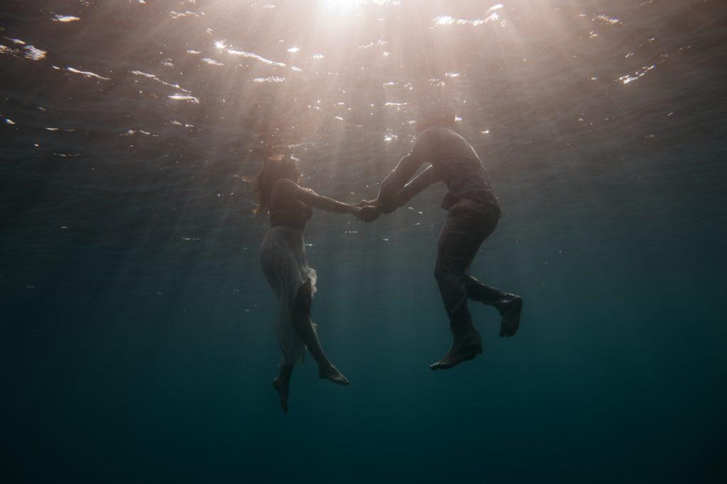Unter Wasser heiraten und Hände haltend auftauchen