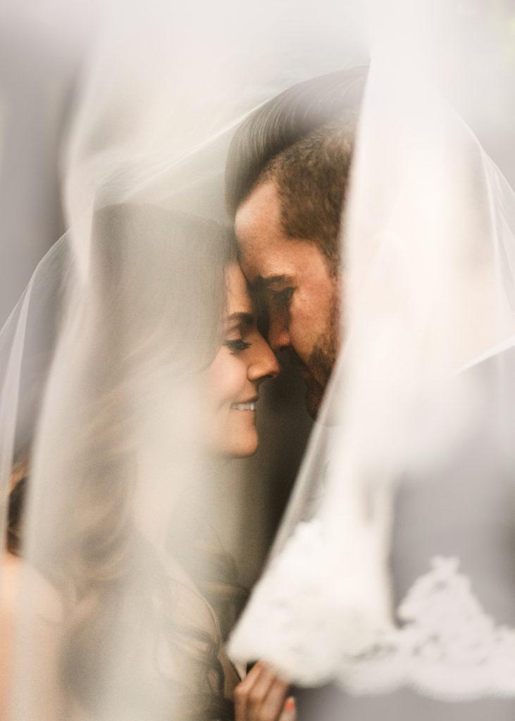 emotionales Brautpaar unter Schleier