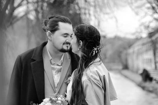verliebtes Brautpaar schaut sich vor einem Wasserschloß in die Augen