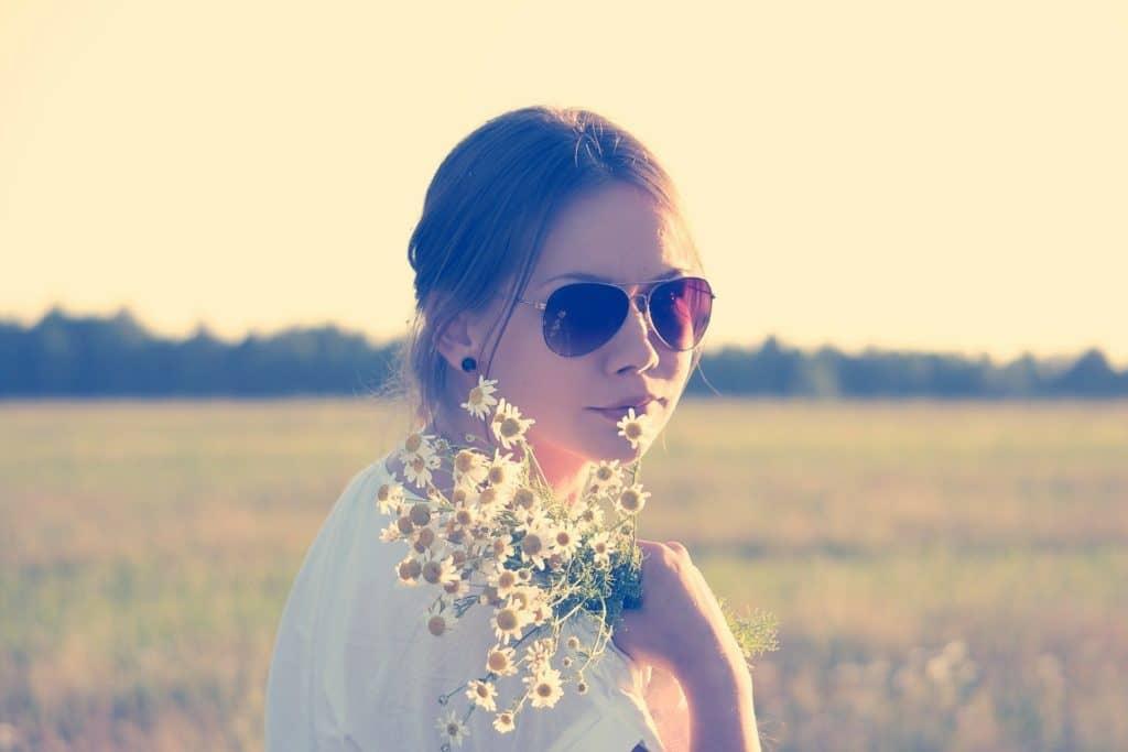 junges Mädchen mit großer Sonnenbrille und Blumen in der Hand
