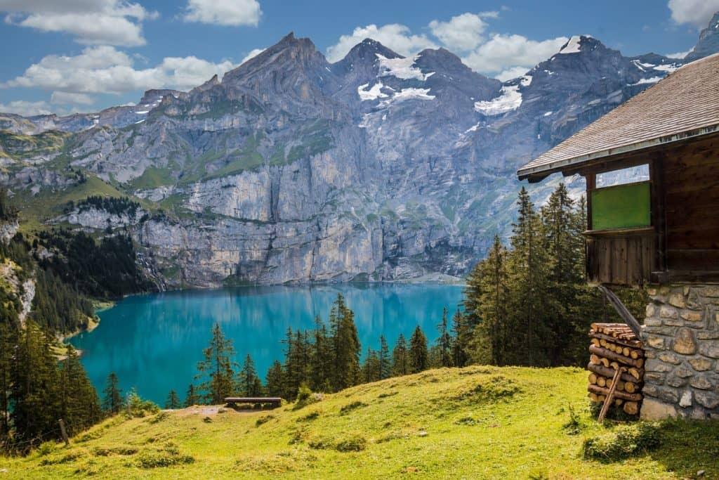 Hütte am See mit Bergen im Hintergrund