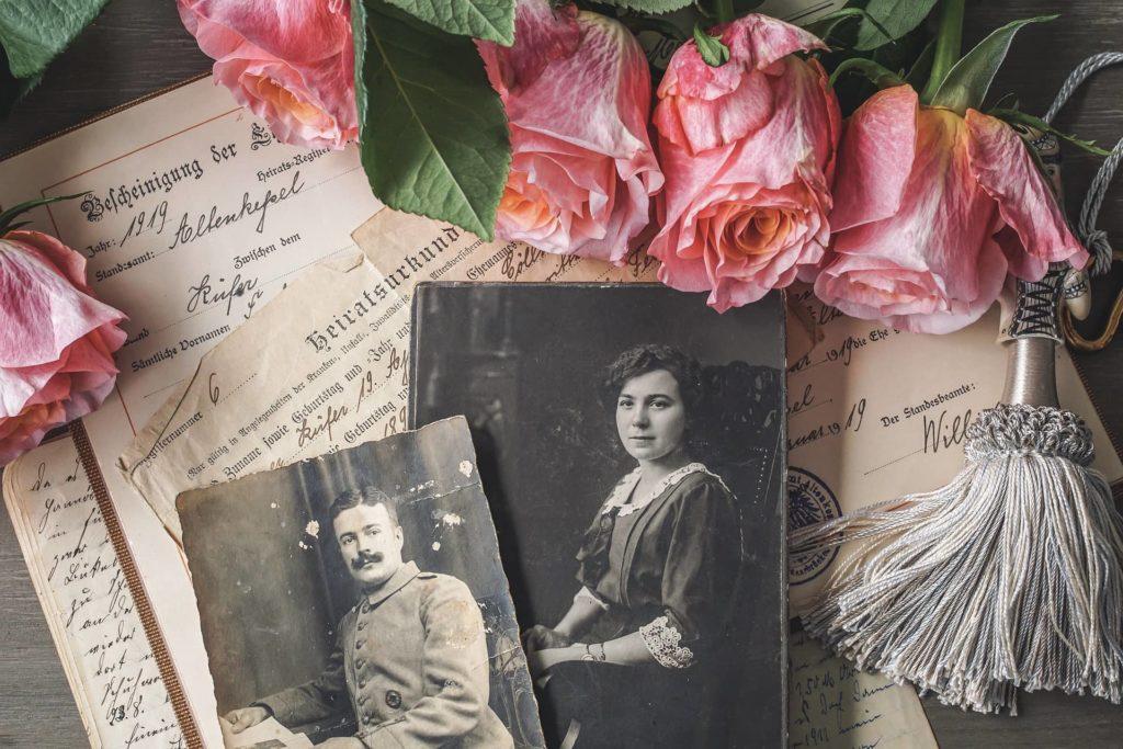 Altertümliche Heiratsurkunde auf einem Tisch mit sehr alten Schwarz-weiß Fotos im Vordergrund