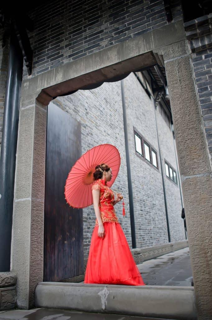 Rote Farbe des Hochzeitskleides bei einer Chinesin mit Bambusschirm