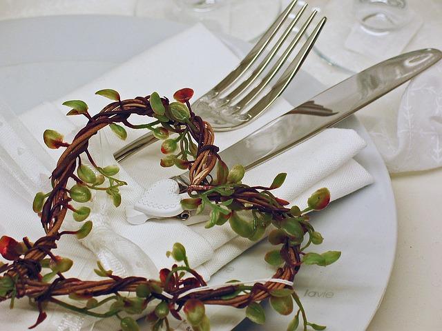 weißer Teller mit Besteck und einem Herz aus Zweigen