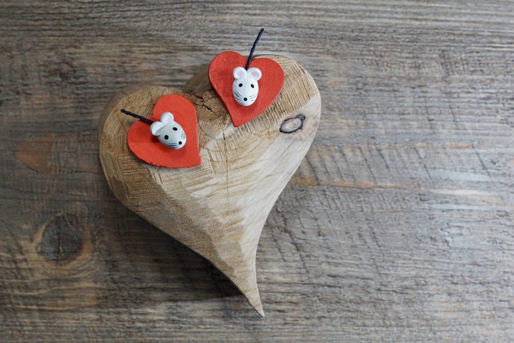 Geschnitztes Herz aus Holz mit gebastelten Mauseköpfen