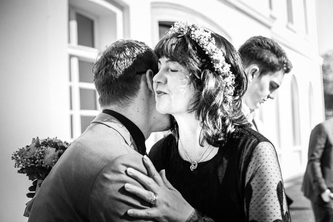 Braut wird von Gast zärtlich umarmt