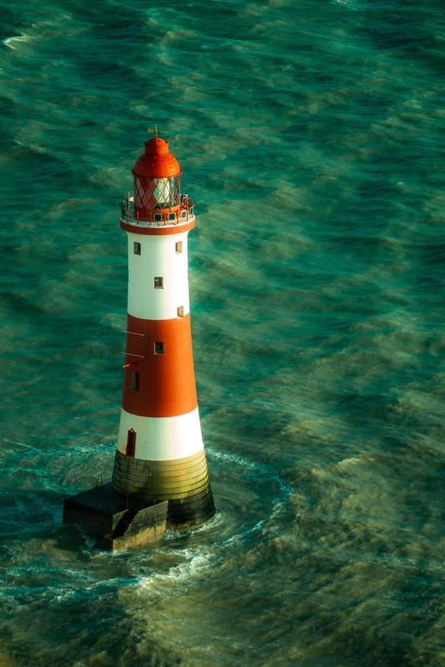 rot weiß gestreifter Leuchtturm im Meer
