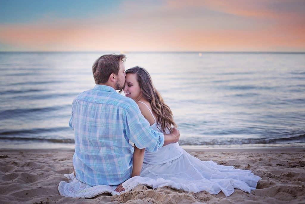 verliebtes Paar sitzt am Strand