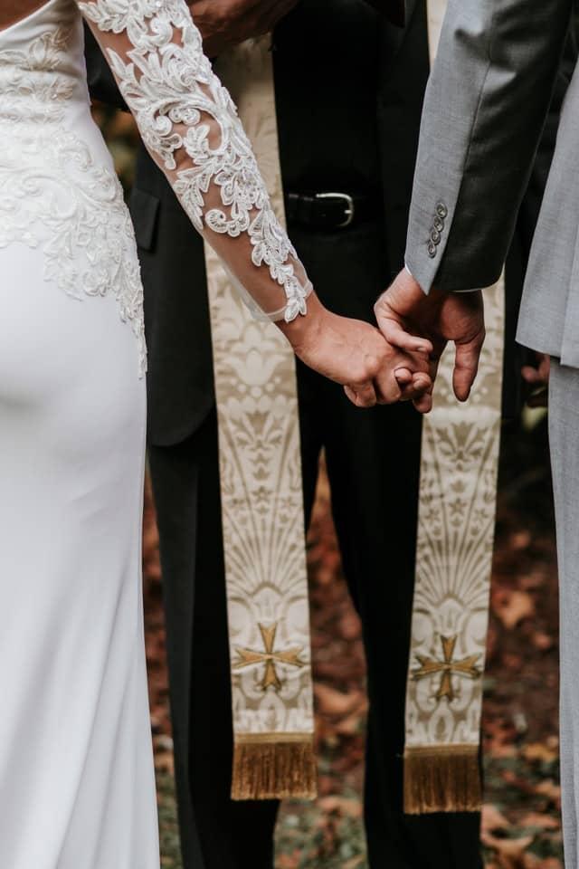 Hochzeitspaar das sich an den Händen hält