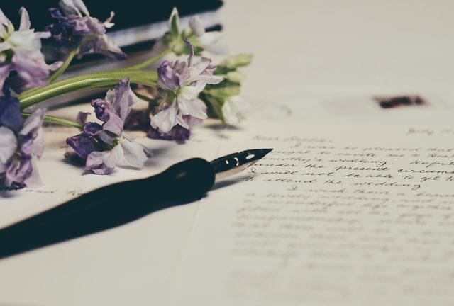 handgeschriebener Brief neben dem ein Füllfederhalter liegt