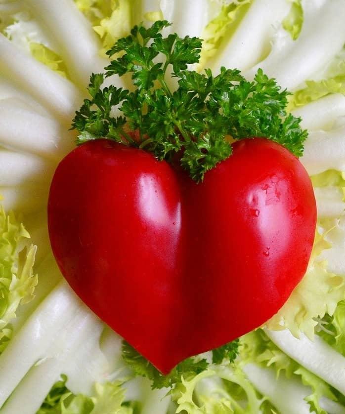 Herzförmige Tomate auf Petersilie angerichtet