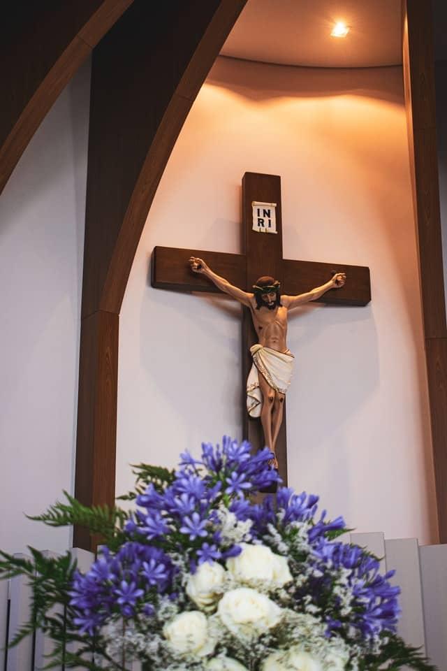 Jesus am Kreuz, im Vordergrund ein Blumenstrauß