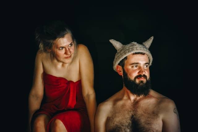 Ein Mann mit einem Wikingerhut auf und eine Frau im roten Handtuch