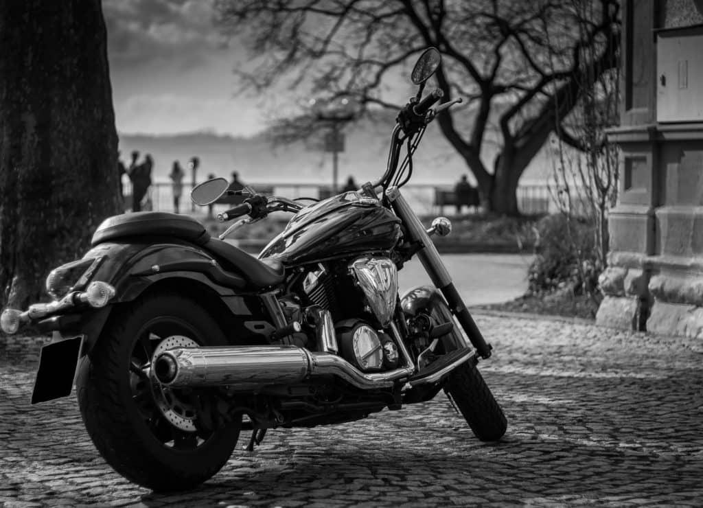 ein Motorrad auf einem Platz, im Hintergrund mehrere Leute