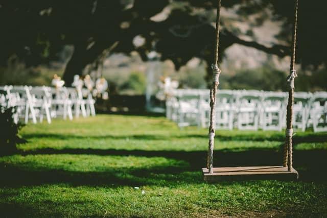 Hochzeitsgesellschaft im Freien, im Vordergrund eine Schaukel