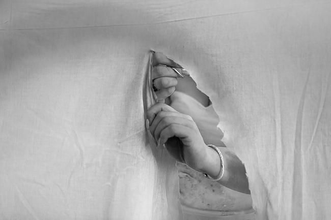 Die Braut trennt mit einer erotischen Handhaltung ein Herz aus einem Stofflaken