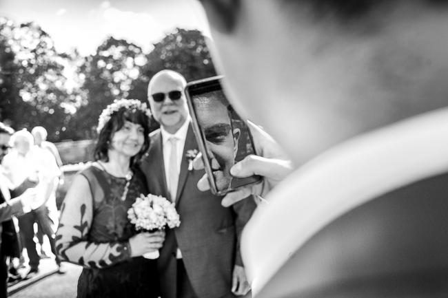 Sohn der Braut fotografiert das Brautpaar mit dem Handy