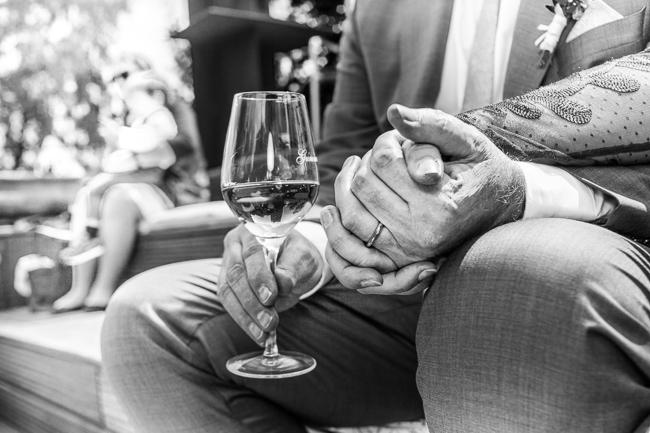 Brautpaar entspannt während der Feier mit Händchenhalten und Wein