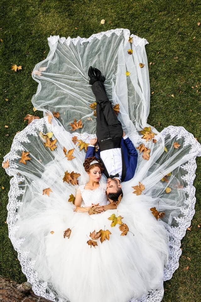 Brautpaar liegt auf der Wiese, er trägt zum Anzug einen Kummerbund