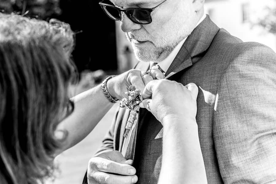 der Fotograf Standesamt Bochum zeigt wie dem Bräutigam eine Boutonniere angesteckt wird