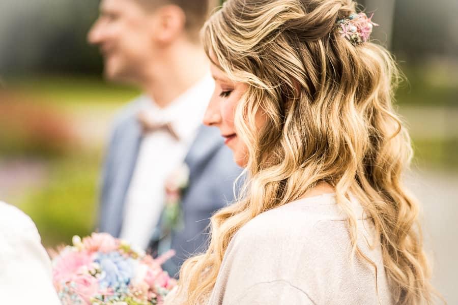 verträumt betrachtet die Braut ihren Brautstrauß