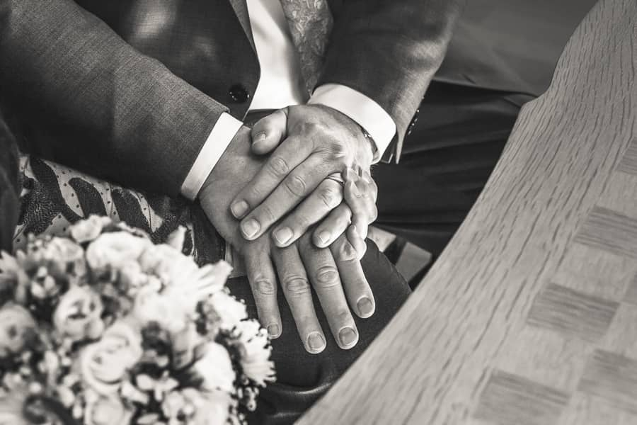 Braut und Bräutigam halten während der Trauung ihre Hände