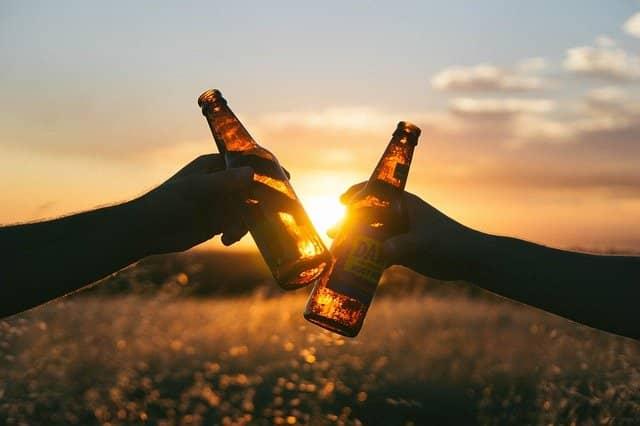 Zwei Leute stoßen mit Bierflaschen auf die Bierhochzeit an