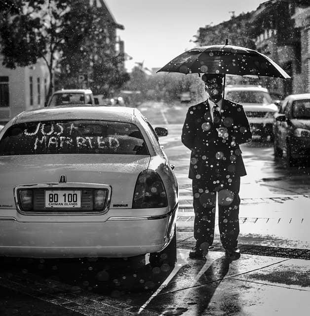 Ein Auto mit der Aufschrift just married, daneben steht ein Mann mit Regenschirm